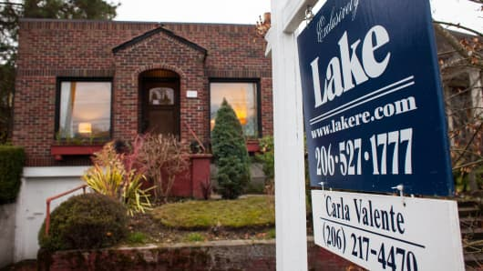 A Lake & Co. Real Estate 'For Sale' sign stands outside of a home in Seattle, Washington, Nov. 19, 2013.